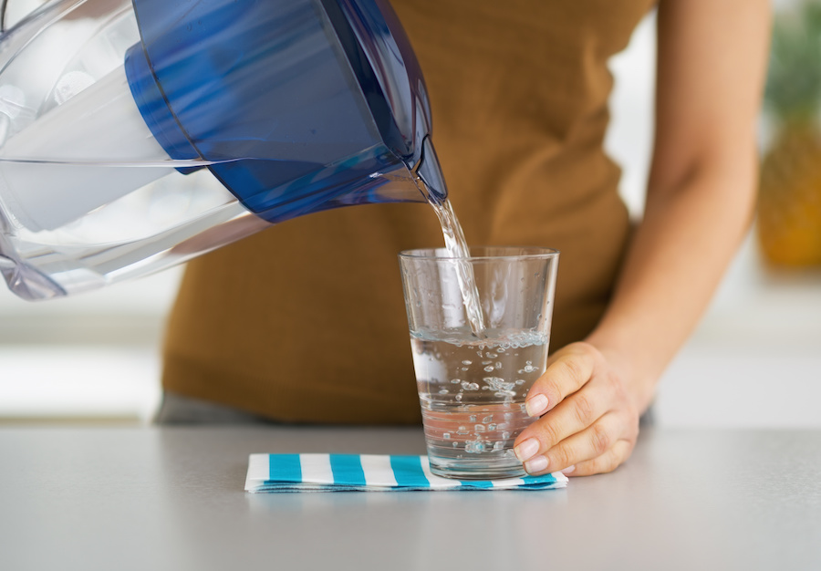 woman pouring water from water filter pitcher